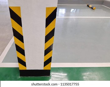 bollards warning striped road yellow-black on both side of concrete pole beside in the car park lot with grey green and white painted on the floor