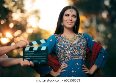 Bollywood Actress Wearing an Indian Outfit with Gold Jewelry Set - Cinema star wearing a salwar kameez with earrings, mangtika and necklace