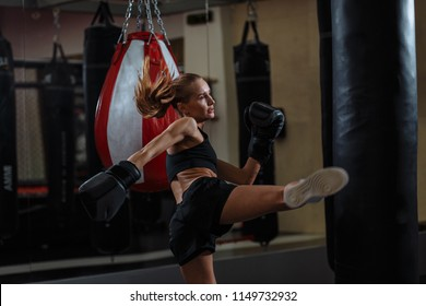 bolnd Female fighter in boxing gloves kicks small boxing bag with high leg kick