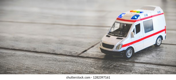 Bologna, Italy, 11 Jan 2018 - ILLUSTRATIVE EDITORIAL of ambulance horizontal background health care toy sirens blue lights copy space .
