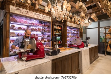 BOLOGNA, ITALY - CIRCA DECEMBER, 2017: Worker cutting ham inside Fico Eataly World, located in Bologna, is the largest agrofood park in the world. Internal view.