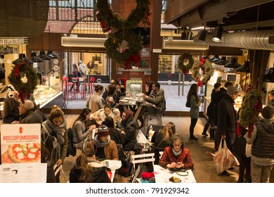 Bologna, Italy - December 2017: People eating in Mercato di Mezzo (The Middle Market) a famous indoor food market in the characteristic medieval city centre of Bologna, Italy
