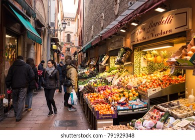 Bologna, Italy - December 2017: People walking in Via Pescherie Vecchie, a famous alley full of traditional stores and food stalls in the characteristic medieval city centre of Bologna, Italy