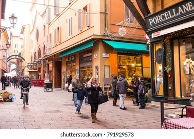 Bologna, Italy - December 2017: People walking in Via Clavature, a famous street full of traditional stores and restaurants in the characteristic medieval city centre of Bologna, Italy