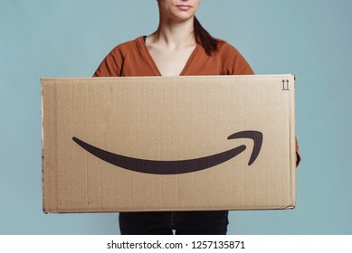 BOLOGNA, ITALY - DECEMBER, 2018: Woman holding big cardboard box from Amazon.