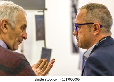 BOLOGNA, ITALY - FEBRUARY 18, 2019: Booth presenter talking with visitor at stand of ANGELO AREZZO SAS in DEVOTIO Religious products and service exhibition