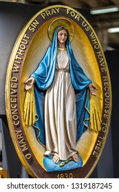 BOLOGNA, ITALY - FEBRUARY 18, 2019: lights are enlightening statue of The Miraculous Medal at stand of ART DEMETZ in DEVOTIO Religious products and service exhibition