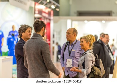 BOLOGNA, ITALY - FEBRUARY 18, 2019: Booth presenter talking with visitor at stand in DEVOTIO Religious products and service exhibition