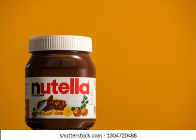 BOLOGNA, ITALY - FEBRUARY, 2019: Nutella jar against orange background. Nutella is manufactured by the Italian company Ferrero and was first introduced in 1965. Illustrative editorial.