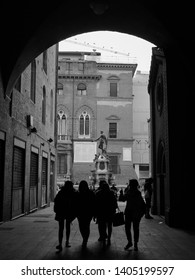 Bologna, Italy - February 26 2019 - A black and white silhouette image of a group of people under an archway near The Fountain of Neptune, which can be seen in the background.