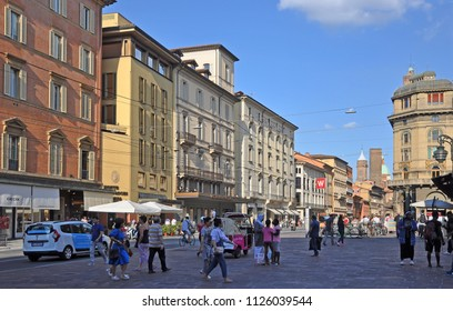 BOLOGNA, ITALY – JULY 14, 2017:  local and tourists in Rizzoli street with  the Garisenda tower in the bottom. One of the city typical street.