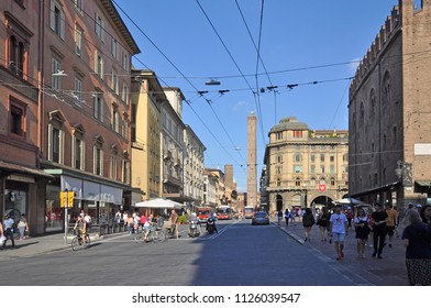 BOLOGNA, ITALY – JULY 14, 2017:  local and tourists in Rizzoli street with  the Asinelli tower in the bottom. One of the city typical street.