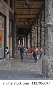 BOLOGNA, ITALY – JULY 15, 2017: local and tourists walking under the portico  in Rizzoli street. One of old the city more typical street.