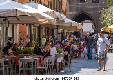 BOLOGNA, ITALY - JULY, 2019: City view of city center with people having lunch outdoors in a sunny day.
