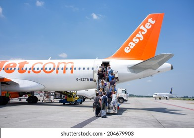 BOLOGNA, ITALY - JUNE 19: People entering an EasyJet plane in Guglielmo Marconi Airport. EasyJet is the low cost airline of the United Kingdom. June 19, 2014 in Bologna, Italy
