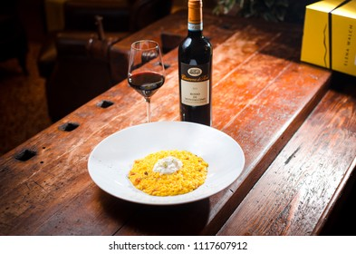 Bologna italy june 21 thursday 2018 - traditional risotto alla milanese and wine bottle on wooden table inside restaurant