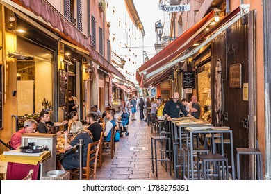 BOLOGNA, ITALY - JUNE 29, 2019: There are many  colorful open-air restaurants and cafes on the Via Pescherie Vecchie in Bologna, Italy.