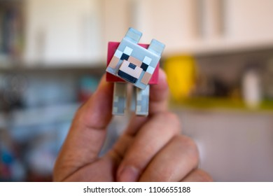 BOLOGNA, ITALY - JUNE 5, 2018: Young boy holding Minecraft toy minifigure at home. Minecraft is a video game created by game designer Markus Persson, better known as Notch. Illustrative editorial.