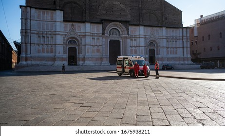 BOLOGNA, ITALY - MARCH 2020: Ambulance and Paramedics in front of San Petronio Cathedral, Piazza Maggiore, during the Covid-19 virus pandemic infection.