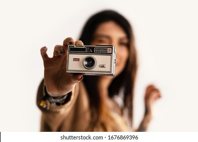 BOLOGNA, ITALY - MARCH, 2020: Young woman holding Kodak Instamatic 100 vintage camera isolated on white background. Illustrative editorial.