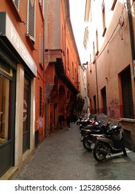 Bologna, Italy - March 30 2018: A narrow cobblestone street between red ochre buildings, with motorcycles parked on one side and a couple walking in the background