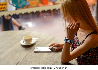 BOLOGNA, ITALY - MAY 17, 2015:  One girl wears the apple watch in a bar using the iphone 6.