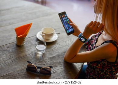 BOLOGNA, ITALY - MAY 17, 2015:  One girl wears the apple watch while using the iphone 6.
