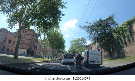 Bologna, Italy - May 19, 2018: POV point of view of a car driving on Bologna city streets. In the weekend traffic on main town avenues, Viale Angelo Masini street, and route Porrettana state highway.