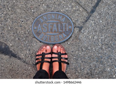 Bologna, Italy : May 25,2011 - Tourist waering sandals on the pavement showing the the embossed name of city of Bologna on a metal plate of Anonima Asfalti