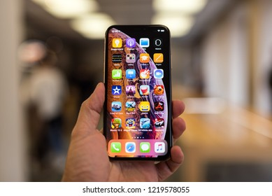 BOLOGNA, ITALY - OCTOBER, 2018: Holding the new iPhones Xs inside Apple Store with customers blurred in the background.