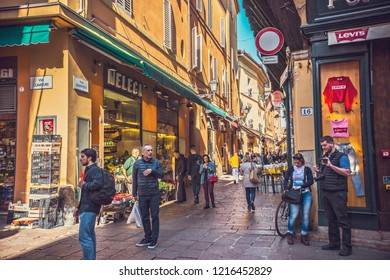 BOLOGNA, ITALY - October 2018: People walking through narrow Bologna street in old town of  Bologna, Italy