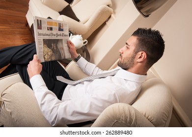 BOLOGNA, ITALY - OCTOBER 27, 2013: Young relaxed businessman reading New York times newspaper sit on armchair.
