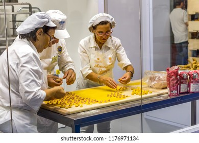 BOLOGNA (ITALY), SEPTEMBER 10, 2018: booth presenters are preparing handmade Bologna Tortellini for visitors at SANA, international exhibition of organic and natural products