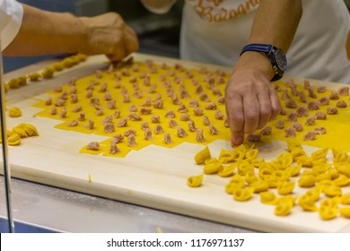BOLOGNA (ITALY), SEPTEMBER 10, 2018: booth presenter is preparing handmade Bologna Tortellini for visitors at SANA, international exhibition of organic and natural products