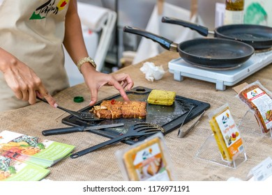 BOLOGNA (ITALY), SEPTEMBER 10, 2018: booth presenter is cooking tofu for tasting for visitors at SANA, international exhibition of organic and natural products