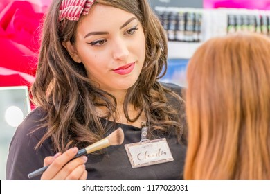 BOLOGNA (ITALY), SEPTEMBER 10, 2018: Makeup artist is making a make up for a visitor at SANA, international exhibition of organic and natural products
