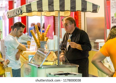 BOLOGNA (ITALY), SEPTEMBER 10, 2018: boy choosing ice cream tastes at SANA, international exhibition of organic and natural products