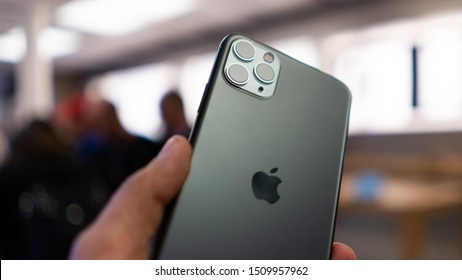 BOLOGNA, ITALY - SEPTEMBER 20, 2019: Holding the new iPhone 11 Pro with triple camera detail inside Apple Store with customers blurred in the background.