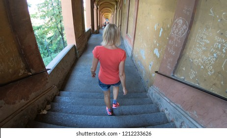 Bologna, Italy - September 29, 2018: top view running woman in San Luca's archway: longest archway of the world from Bologna city to San Luca Sanctuary on Colle della Guardia hill.