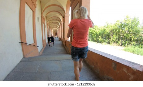 Bologna, Italy - September 29, 2018: a sporty woman running under San Luca's porch: the longest portico in the world leading to the San Luca Sanctuary on Colle della Guardia.