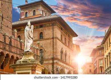 Bologna, Italy. Statue of San Pietro on Piazza di Porta Ravegnana. Evening Sunset among terracotta buildings in old town.