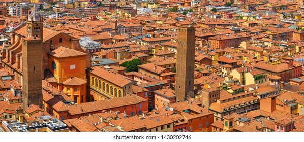 Bologna, Italy. Top view of old town with terracotta houses, streets, towers, ancient cathedral and housetops. Sunny day urban italian landscape.