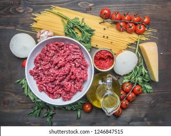 bolognese pasta cooking concept, raw minced meat, tomato paste, cherry tomatoes, pasta, parmesan, onions, garlic, herbs and herbs, oil and cold leaves on a rustic wooden background