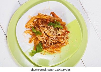 Bolognese pasta in green plate over white wooden board. Horizontal overhead shot