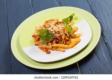 Bolognese pasta in green plate over wooden board. Horizontal shot