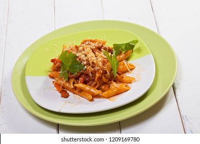 Bolognese pasta in green plate over white wooden board. Horizontal shot