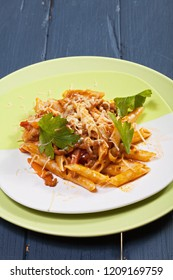 Bolognese pasta in green plates over wooden board. Vertical shot