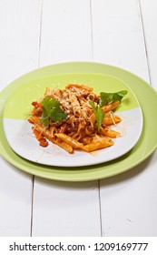 Bolognese pasta in plates over white wooden board. Vertical shot