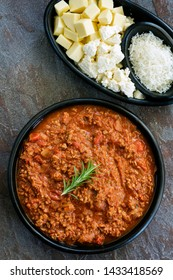 Bolognese sauce with Italian cheeses, top view, isolated on white.  Mozzarella, ricotta and parmesan.  Black rustic dishes on slate.