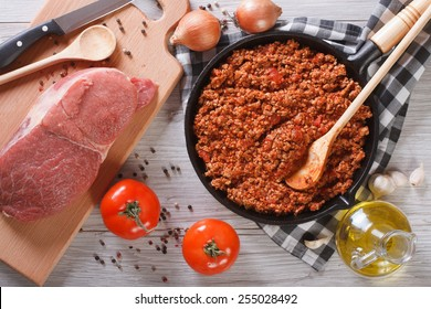Bolognese sauce in a pan and ingredients on the table. horizontal view from above